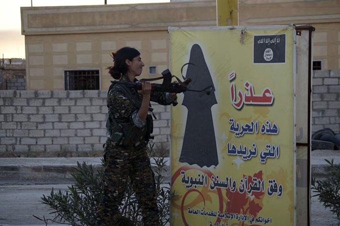 Kämpferin der YPJ zerstört die Hinweistafel des IS zur Kleiderordnung für Frauen | Foto: ANF